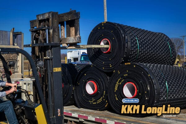 Stall mat rolls being loaded on to a flat bed trailer with a forklift.